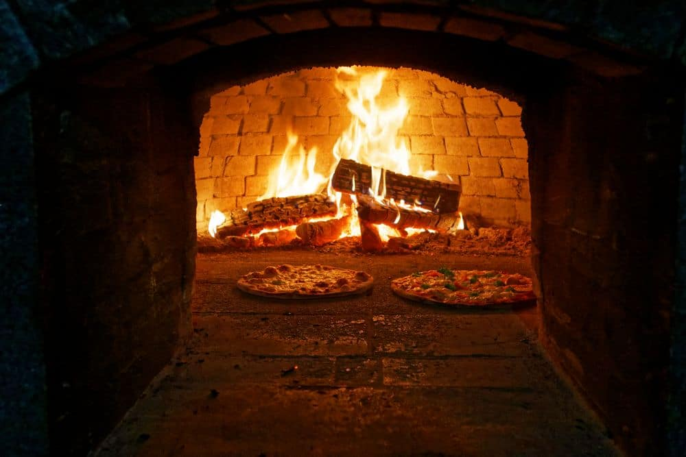 Italian pizza is cooked in a wood-fired oven