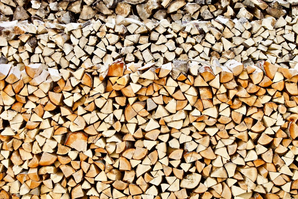 Stacked firewood close-up. Firewood storage close up. Stocks of wooden logs close-up. Chopping wood. Logging in the village. Rustic lifestyle. Woodpile with firewood full frame image. Wooden texture. Wooden pattern. Abstract backgrounds and textures. Wooden wall close up.
